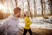 Couple Running Side By Side In Woods In Winter. poster