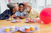 Front view of senior African-American man and woman kissing their grandson for his birthday party. A poster