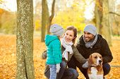family, pets and people concept - happy mother, father and little daughter with beagle dog over autu poster