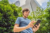 Man Tourist Using Navigation App On The Mobile Phone. Navigation Map On A Smartphone In A Big City poster