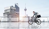 Man Wearing Business Suit Riding Bicycle On Penthouse Balcony. Young Cyclist With Suitcase On Backgr poster