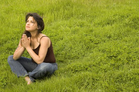 image of women rights  - Young woman sitting in praying pose copyspace to the right - JPG