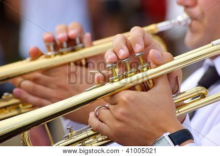 Musicians playing on trumpets