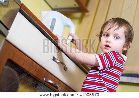 Little Baby Boy Is Reaching Eletrical Kettle With Hot Water