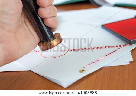 Close-up Of Notary Stamping An Important Document