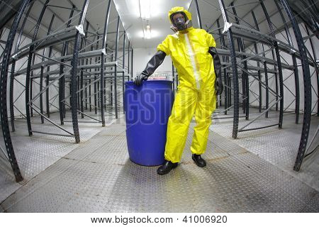 worker in safety - protective uniform,standing at blue barrel - portrait