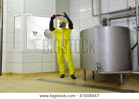 two professionals in protective uniforms working in  industrial space