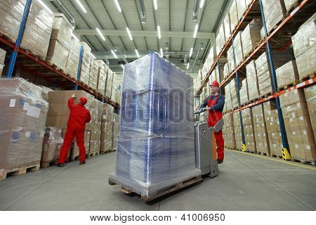logistics - management of the flow of resources  - two workers in uniforms and safety helmets working in storehouse