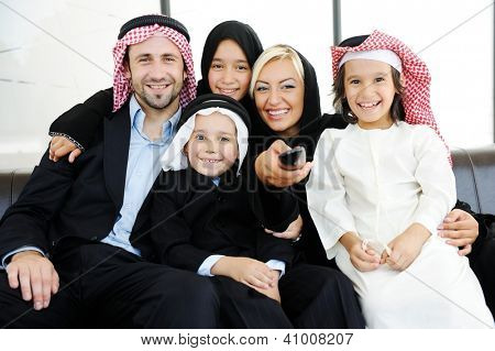 Arabic Muslim family father and mother with children watching television