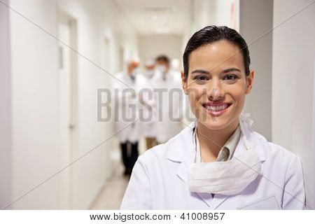 Portrait of happy young female doctor with colleagues in background