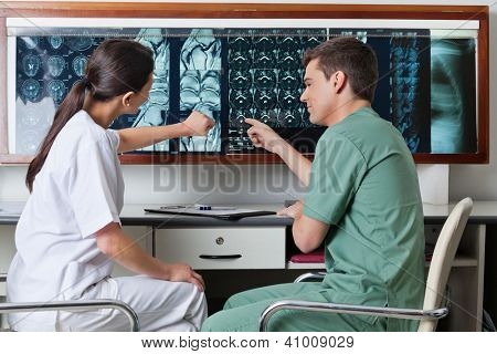 Two medical technicians pointing at MRI x-ray of patient