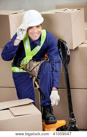 Portrait of mid adult foreman with fork pallet truck in warehouse