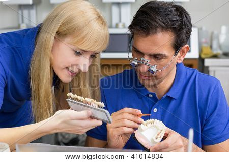 Two Dental Technicians Choosing The Right Colour For Dental Porcelain