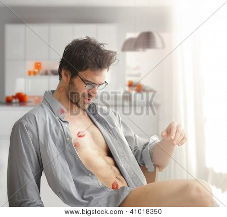 Portrait of sexy man at home with shirt open and lipstick kiss marks on his bare body and playful fun expression