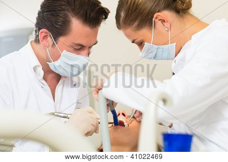 Female patient with dentist and assistant in a dental treatment, wearing masks and gloves