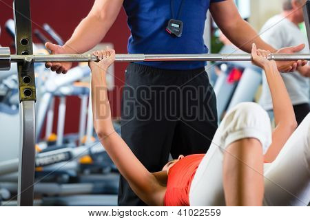 Woman with her personal fitness trainer in the gym exercising with dumbbells, she is using barbell on a weight bench