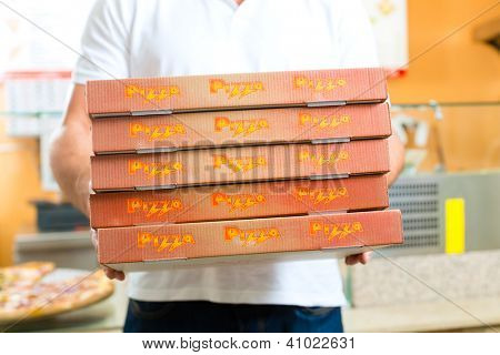 Man holding several pizza boxes in hand ready for delivery