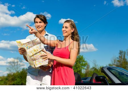 Young hip couple - man and woman - with cabriolet convertible car in summer on a day trip, they obviously looking for the right way