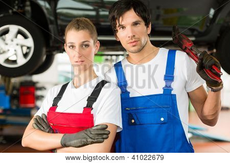 Young woman and man in blue overall - mechanic - stand with in front of a jacked car in a service station