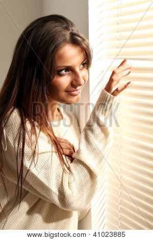 Beautiful young brunette woman in white near window