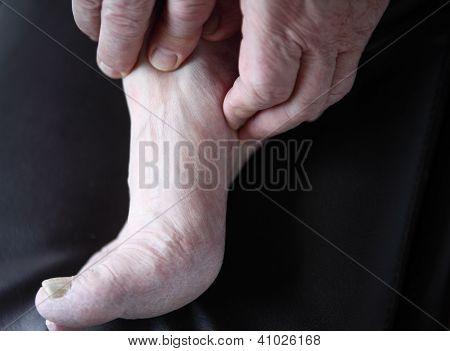 homem verifica seu pé dolorido