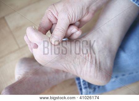 man rubbing his athletes foot