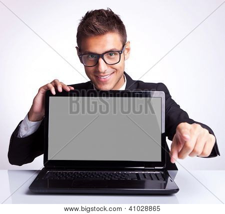Business man sitting at office desk with laptop computer facing the camera and pointing his finger to you