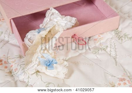 Bridal garter with blue bow in a pink gift box
