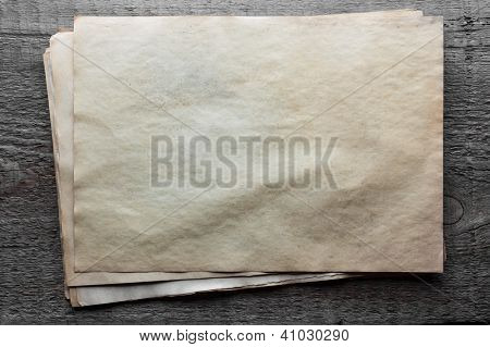 stack of old papers on dirty wooden background