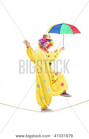 Full length portrait of a happy male clown with umbrella walking on a rope isolated on white background