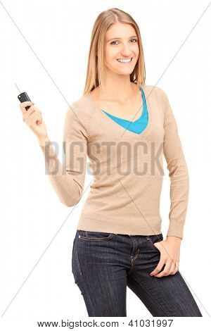 Satisfied young female holding a car key isolated on white background