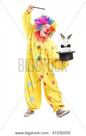 Full length portrait of a circus clown performing a magic trick with a top hat and a rabbit isolated on white background