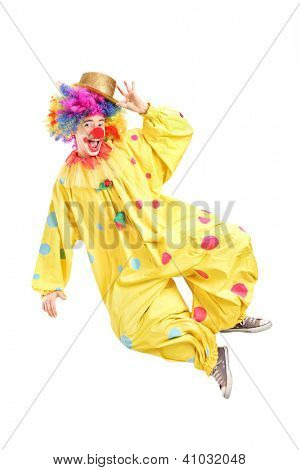 Full length portrait of a male clown jumping and gesturing isolated on white background