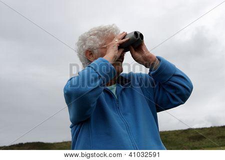 A Senior Lady Using Binoculars
