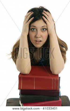 Female student resting arms on stack of books with overwhelmed expression