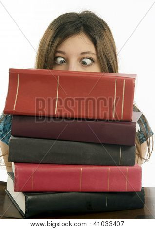 Female student with eyes crossed looking over stack of books