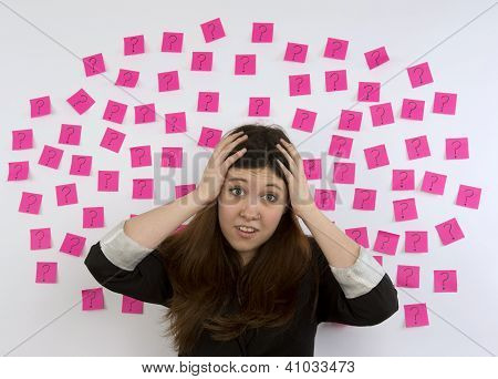 Young woman with nose ring with pink sticky notes and question mark thinking about decision making