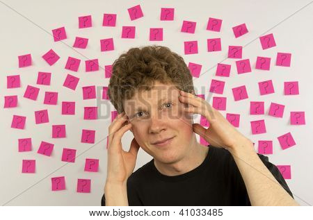 Young man with with pink sticky notes and question mark thinking about decision making