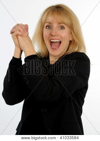 Blond business woman cheering with hands clasped together