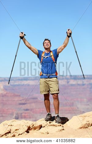 Success winner hiker cheering happy. Man hiking reaching Grand Canyon south rim summit goal. Young fit strong caucasian man.