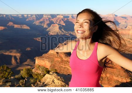Happy freedom woman tourist in Grand Canyon smiling free in happiness during summer travel trip in Grand Canyon, South Rim, Arizona, USA.