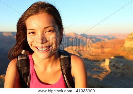 Hiker woman smiling natural canidid in happy outdoor portrait. Aspirational lifestyle image of hiking young multiracial female hiker in Grand Canyon, South Rim, Arizona, USA.