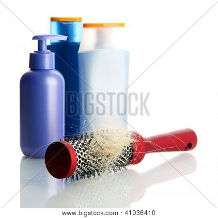 comb brush with lost hair and cosmetics bottles, isolated on white