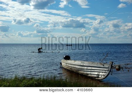 Lake View With Old Fishing Boat And Washing Woman