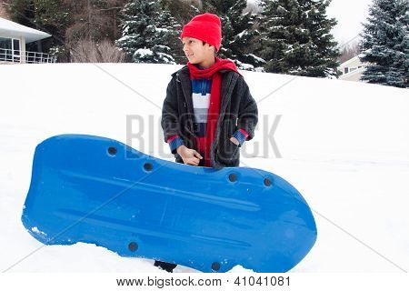 East Indian Boy Toboganning In The Snow