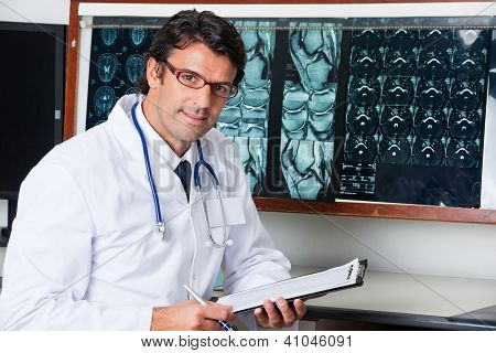 Portrait of mixed race male radiologist sitting at desk with clipboard