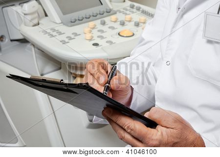 Midsection of male doctor writing on clipboard with ultrasonic machine in background