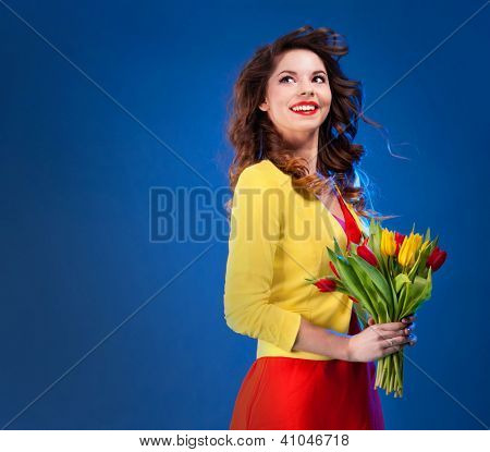 Colorful fresh portrait of a beautiful happy young woman holding flowers