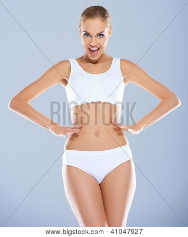 Vivacious woman with a beautiful figure posing in skimpy sportswear with her hands on her waist