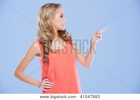 Attractive blonde woman standing sideways pointing to the right of the frame with her index finger towards blank copyspace, isolated on blue
